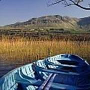 Row Boat Amongst Reeds On A Lake Art Print