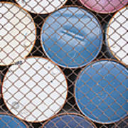 Rows Of Stacked Barrels Behind A Fence Art Print