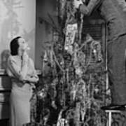 Woman Assisting Man Placing Star On Top Of Christmas Tree, (b&w) Art Print by George Marks