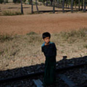 A Boy In Burma Looks Towards A Train From The Shadows Art Print
