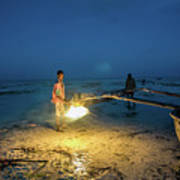 A Local Fisherman Uses Flame To Repair His Boat At Sunset Art Print