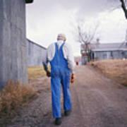 An Elderly Farmer In Overalls Walks Art Print