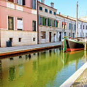 boat in a canal of the colorful italian village of Comacchio in  Art Print