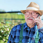 Senior Gardener Talking On The Phone With A Client. Art Print