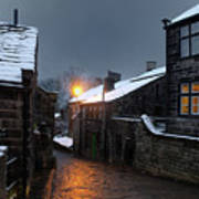 The Village Of Heptonstall In The Snow At Night With Lamps Shini Art Print