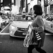 woman crossing crosswalk in front of yellow cabs in the evening in Times Square New York City USA Art Print
