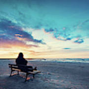 Man In Hood Sitting On A Lonely Bench On The Beach Art Print