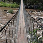 A Long Suspension Bridge Over A River Art Print
