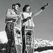 Couple Holding Snowshoes, Woman Pointing Art Print