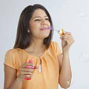 Young woman blowing soap bubbles Art Print