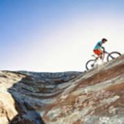 A man riding a mountain bike on an extreme sandstone ledge Art Print