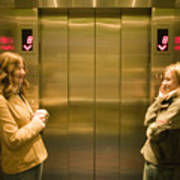 Two young women waiting in elevator Art Print