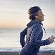 Woman jogging while listening music at beach against sky Art Print