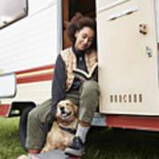 Woman with dog reading book in motor van Art Print