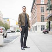 Young man standing on city sidewalk Art Print