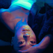Young woman lying upside down with hand on forehead in neon room Art Print