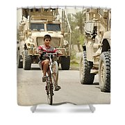 An Iraqi Boy Rides His Bike Past A U.s Shower Curtain by Stocktrek Images