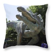 A Dinosaur Exhibit With Visitors In The Universal Studios Singapore Throw Pillow