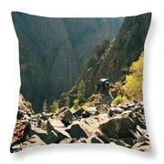 A Man Navigates A Rock Scree Field Throw Pillow