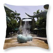 A Water Fountain With Dinosaur Eggs And Dinsosaurs In Universal Studios Throw Pillow