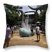 A Water Fountain With Dinosaur Eggs In Universal Studios Singapore Throw Pillow