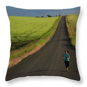 A Woman Running On A Dirt Road Throw Pillow
