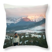 A Woman Stands Against A Snowy Mountain Throw Pillow