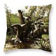 A Wooden Sculpture Inside A Garden Throw Pillow