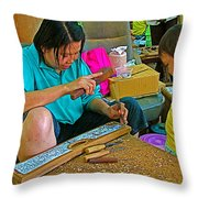 Child Watches As Mom Works In Teak Wood Carving Shop In Kanchanaburi-thailand Throw Pillow