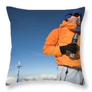 Dressed In Orange, A Skier Sips A Warm Throw Pillow