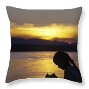 Young Girl Silhouetted Reading A Book On The Beach At Sunset Throw Pillow