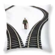 Figurine Between Two Tracks Leading Into Different Directions Symbolic Image For Making Decisions. Throw Pillow by Bernard Jaubert