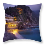 A Building Illuminated At Night Along Throw Pillow