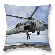 A Naval Aircrewman Is Hoisted Into An Throw Pillow