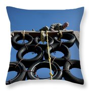 A Soldier Climbs Over A Tire Tower Throw Pillow