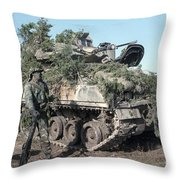 A Soldier Stands Beside A Camouflaged Throw Pillow