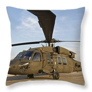 A Uh-60 Black Hawk Parked At A Military Throw Pillow