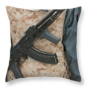 An Ak-47 Rests On The Sling Of An Throw Pillow