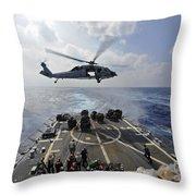 An Mh-60r Sea Hawk Transfers Supplies Throw Pillow