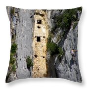 Climber Near Prehistoric Cliff Dwelling Throw Pillow