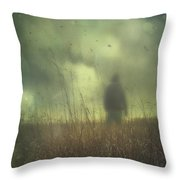 Hooded Man Walking In Field With Storm Clouds Throw Pillow by Sandra Cunningham
