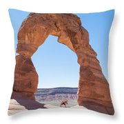 A Couple Kissing Under Delicate Arch In  The Arches National Par Throw Pillow