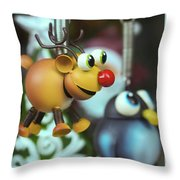 A Rudolph The Red Nosed Reindeer Ornament With A Penguin Throw Pillow