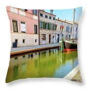 boat in a canal of the colorful italian village of Comacchio in  Throw Pillow