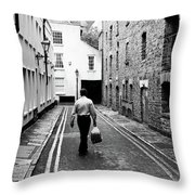 Man Walking With Shopping Bag Down Narrow English Street Throw Pillow