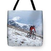 A Mountain Biker Rides Through The Snow Tote Bag