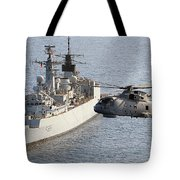 A Royal Navy Merlin Helicopter Passes Over Hms Cumberland Tote Bag