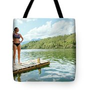 A Woman Is Standing On A Jetty Tote Bag