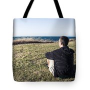 Caucasian Traveler Relaxing On Grass Outdoors Tote Bag
