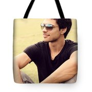 Man In Twenties Relaxing Outside On Green Grass Tote Bag
